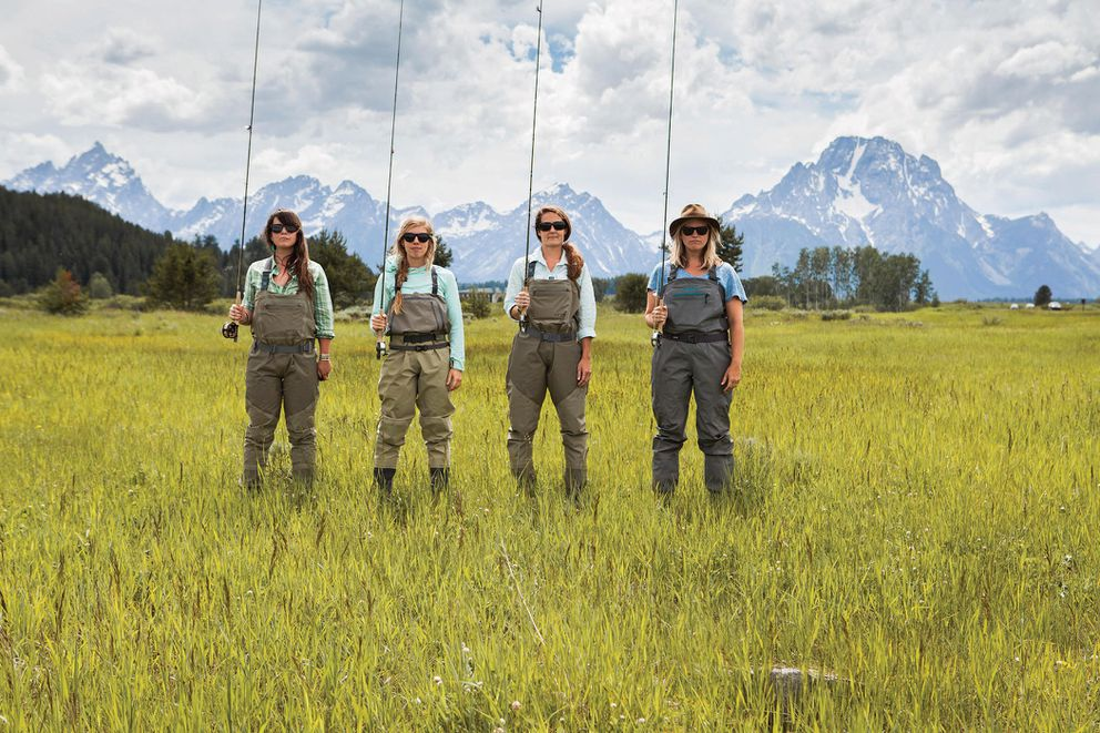 A handout photo of, from left: Becca Skinner, Heidi Dooley, Em Loerke and Molly Robeson dressed for fly fishing, with the Grand Tetons in the background in 2015.  (Becca Skinner, via Orvis via The New York Times)