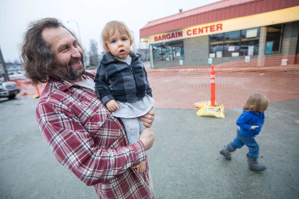 Eagle River Pawn Shop owner Glen Keller holds his granddaughter Psalm Keller, 1, in the parking lot outside his shop on Wednesday, Dec. 5, 2018. Keller was planning on re-opening after Friday's magnitude 7.0 earthquake, until an aftershock Monday collapsed the building's roof. (Loren Holmes / ADN)