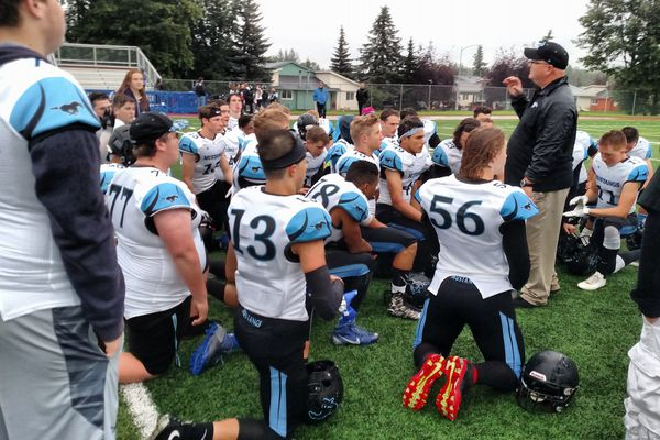 The Chugiak Mustangs listen to coach Roger Spackman after Friday night's 20-6 win over defending state champion East at East High. (Photo by Stephan Wiebe)