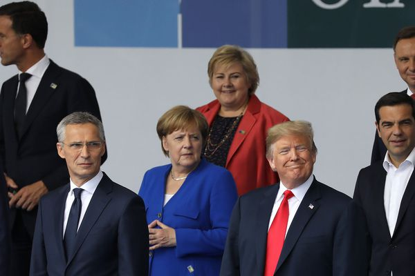 President Trump, front right, German Chancellor Angela Merkel, center, and NATO Secretary General Jens Stoltenberg, left, stand for a photo during the NATO summit in Brussels on Wednesday. MUST CREDIT: Bloomberg photo by Marlene Awaad