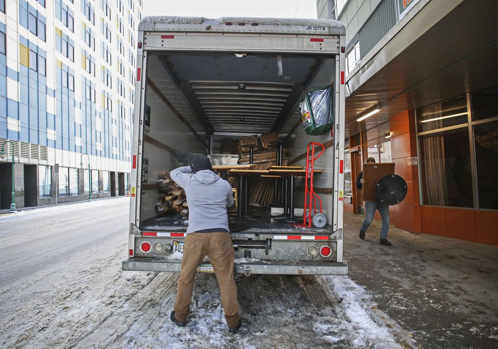 Tyler Schlereth, center, loads a table into a moving truck as Jesse Biddle carries another one over from Matanuska Brewing Company in downtown Anchorage on Saturday, Nov. 28, 2020. The flooring and tables from the downtown location will be used for the outdoor dining section of the midtown location to comply with the newest pandemic emergency mandates. The downtown location has been shut down since about March, Schlereth said. (Emily Mesner / ADN)