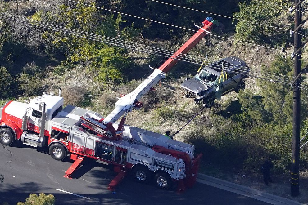 Workers move a vehicle after a rollover accident involving golfer Tiger Woods Tuesday, Feb. 23, 2021, in Rancho Palos Verdes, Calif., a suburb of Los Angeles.. Woods suffered leg injuries in the one-car accident and was undergoing surgery, authorities and his manager said. (AP Photo/Mark J. Terrill)