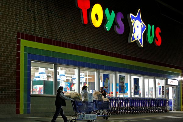 FILE PHOTO: Consumers leave a Toys R Us store with full shopping carts after shopping on the day dubbed