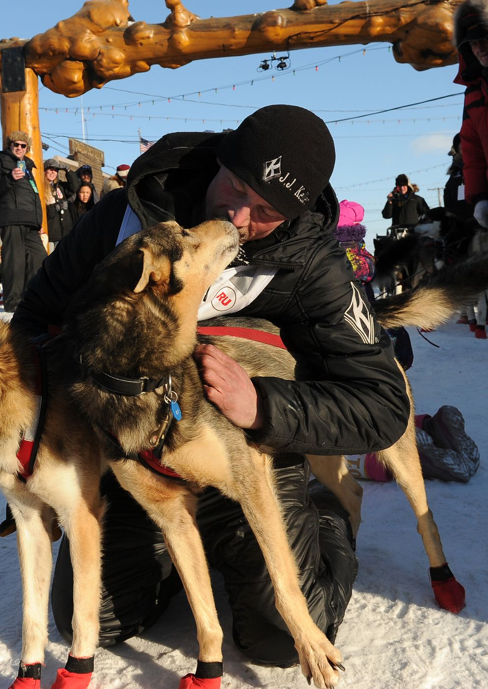 Dallas Seavey spends time with one of his dogs after finishing the Iditarod in second place Tuesday in Nome.  (Bob Hallinen / Alaska Dispatch News)