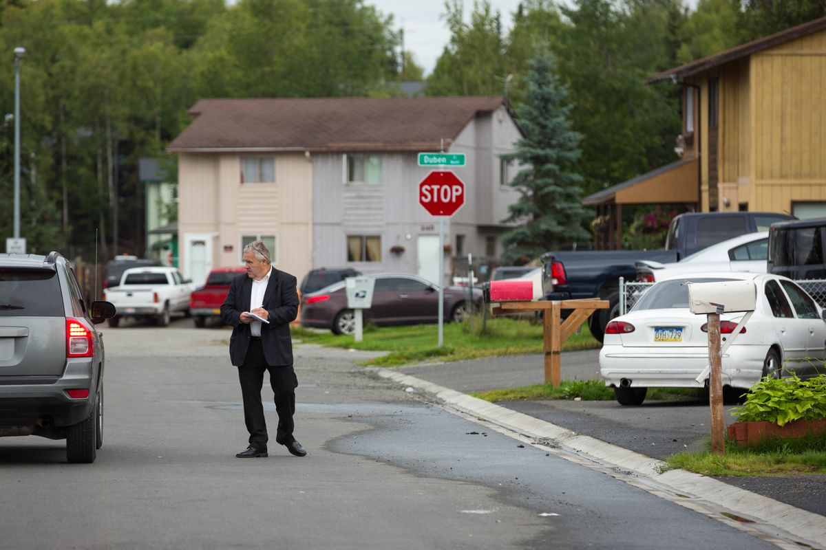 Anchorage police talk to residents Friday morning along Bolin Street in Muldoon after a man was shot and killed nearby. (Loren Holmes / Alaska Dispatch News)