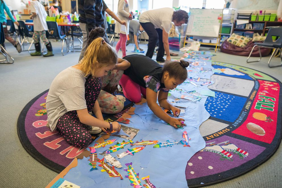 Campbell Elementary second-graders Sommer Szymanski, left, and Manaia Butler work on a timeline Friday, May 5, 2017. (Loren Holmes / Alaska Dispatch News)