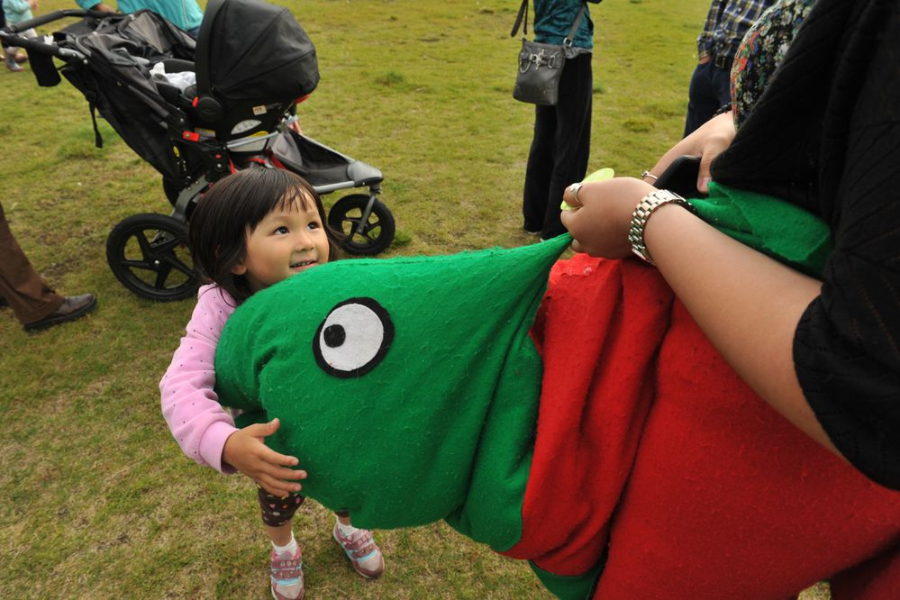 Sophia Dai hugs a salmon worn by Carla Pasillas as people gathered at Cuddy Family Midtown Park in Anchorage, Alaska to celebrate Alaska Wild Salmon Day on Thursday, August 10, 2017. The event featured free barbecued salmon, music by The Hannah Yoter Band, fish painting and informational booths. (Bob Hallinen / Alaska Dispatch News)