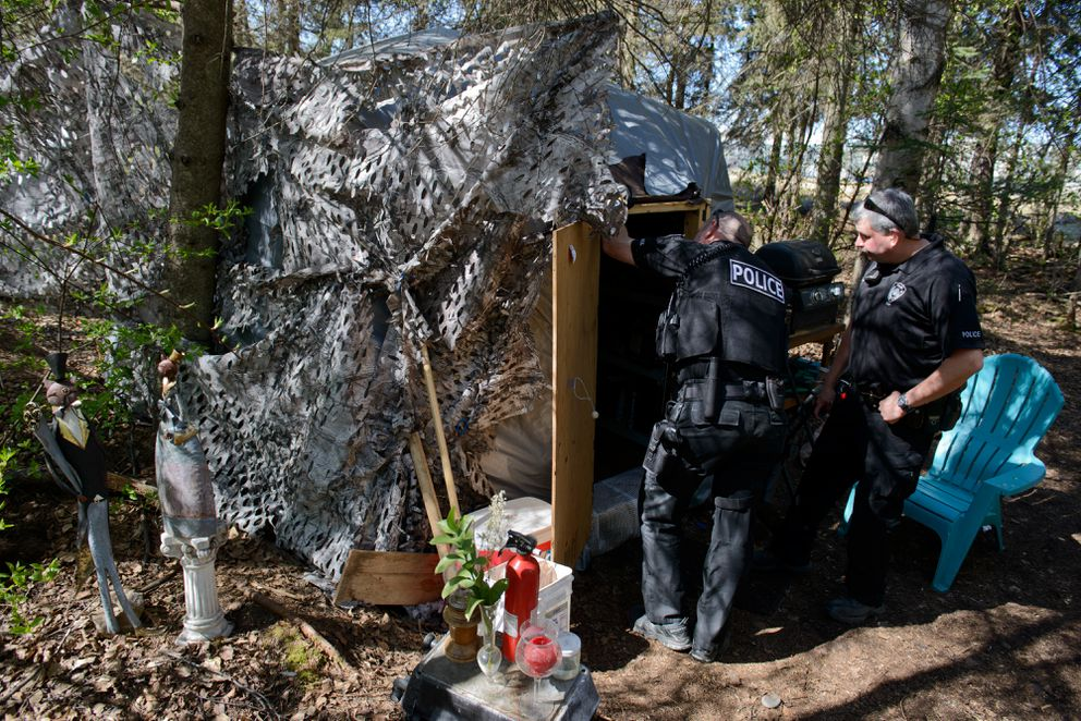 Anchorage police Sgt. Mark Bakken, right, and another officer who did not want to be identified visit a tent along the Chester Creek greenbelt on May 12 to warn Matthew Strametz that he must leave within 15 days. (Marc Lester / Alaska Dispatch News)