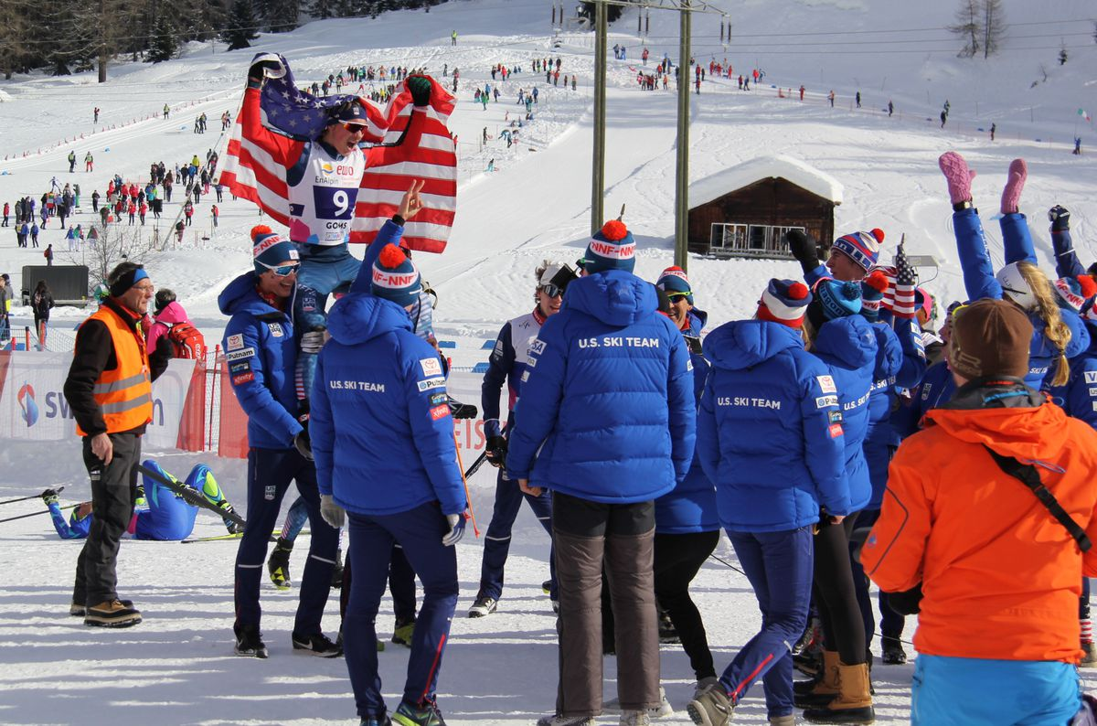 Gus Schumacher is hoisted up with the American Flag after the U.S. World Junior's relay team of Luke Jager, Hunter Wonders, Schumacher and Ben Ogden, placed second in the world championships on Saturday in Goms, Switzerland. (Photo by Glenn Gellert)