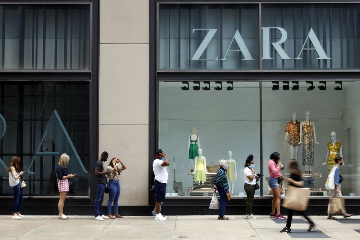 Shoppers wait in line outside a Chicago downtown retail store as others pass by, Wednesday, May 26, 2021. Retailers are seeing an eager return to their stores after months of watching their customers focus on online buying during the pandemic. (AP Photo/Shafkat Anowar)