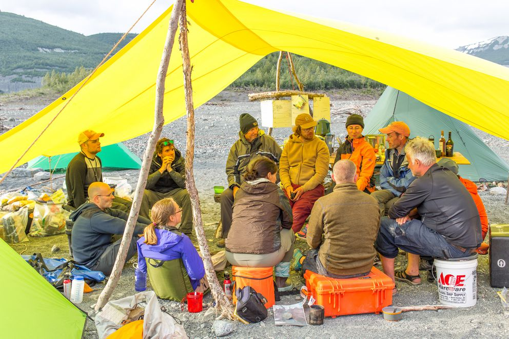 The earth science team discusses their daily findings, discoveries, insights, and makes plans for the following day. Three successful expeditions, to study the landslide generated tsunami, in Icy Bay, Alaska were undertaken in summer 2016. The main expedition, in June, consisted of fourteen people. (Bjorn Olson / Ground Truth Trekking)