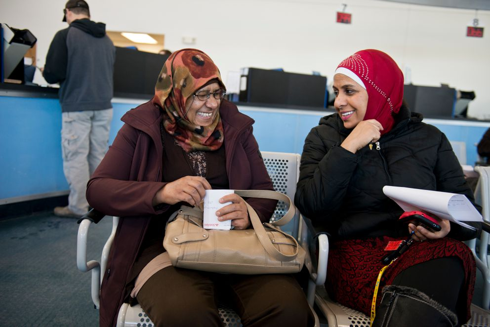 Husniyah Aljaanhi, 65, laughs with Zabeeba Mohamed on Feb. 2, 2017. Mohamed joined Aljaanhi at the DMV to assist with translating to Arabic.  (Marc Lester / Alaska Dispatch News)