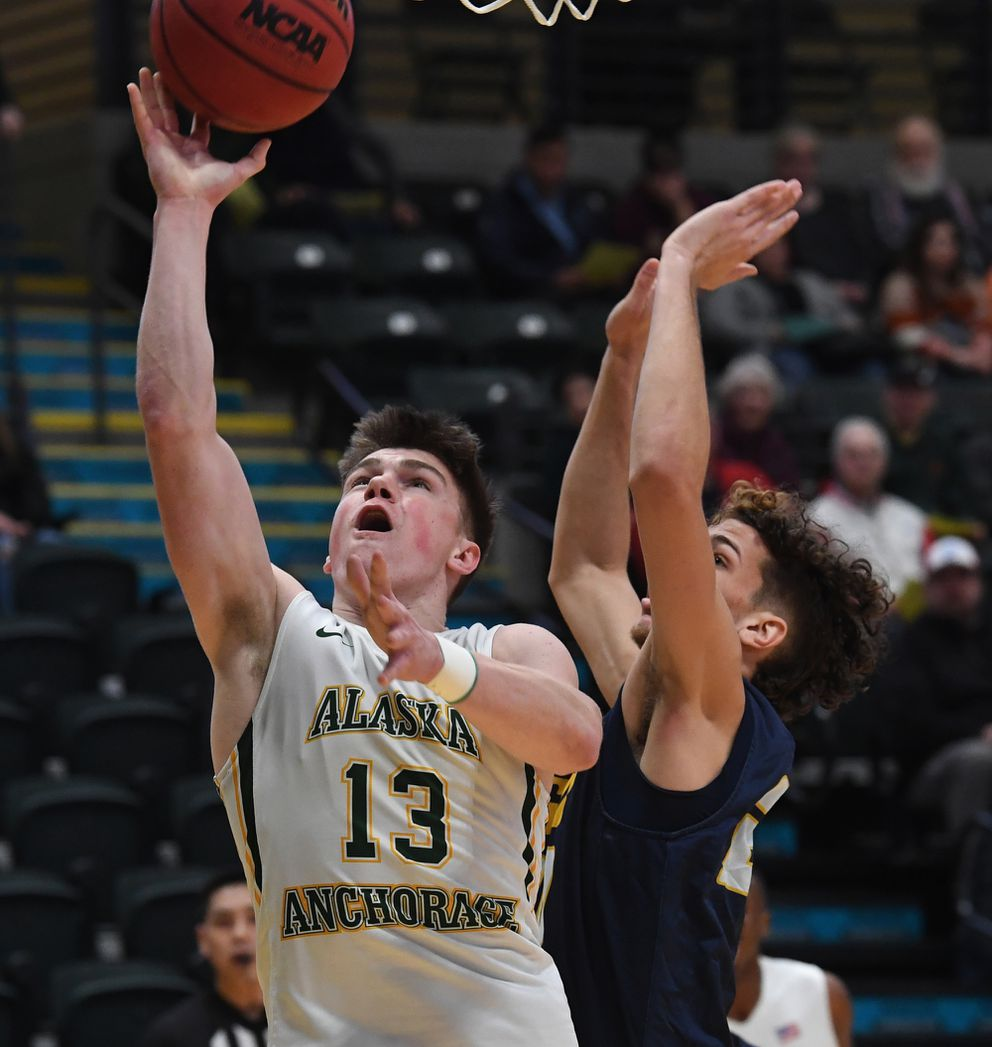 Tobin Karlberg of UAA goes for a basket as Stevie James defends. (Photo by Bob Hallinen)