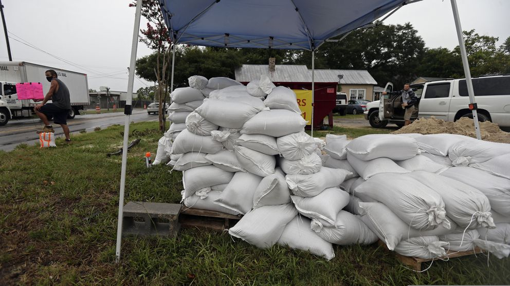Michael Bledsoe, far left, sells sandbags as Tropical Storm Isaias approaches in Wilmington, N.C., Monday, Aug. 3, 2020. (AP Photo/Gerry Broome)