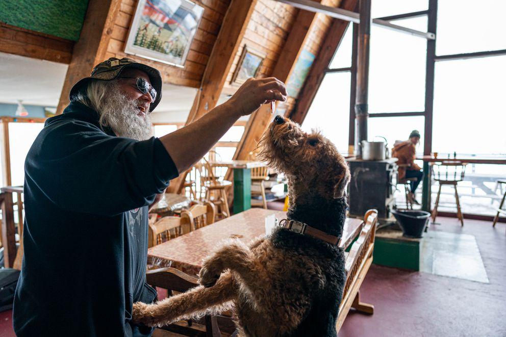 Hatcher Pass Lodge caretaker Jeff Polk gives his dog Loki a treat on Wednesday. (Loren Holmes / ADN)