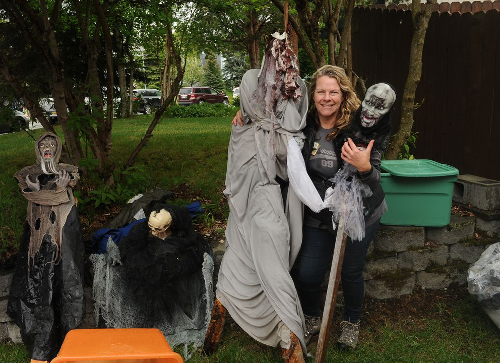 Margi Petersen poses with some of for her vast collection of Halloween decorations during the Kempton Hills neighborhood garage sale on Saturday, May 21, 2016. The huge event filled the neighborhood with people and cars. (Bob Hallinen / Alaska Dispatch News)