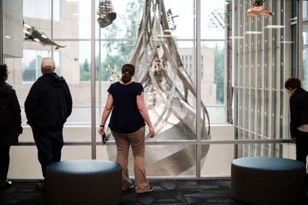 """Patrons observe a hanging sculpture titled """"Portal of Perception"""" from the 2ndfloor of the Loussac Library. (Young Kim / Alaska Dispatch News)"""