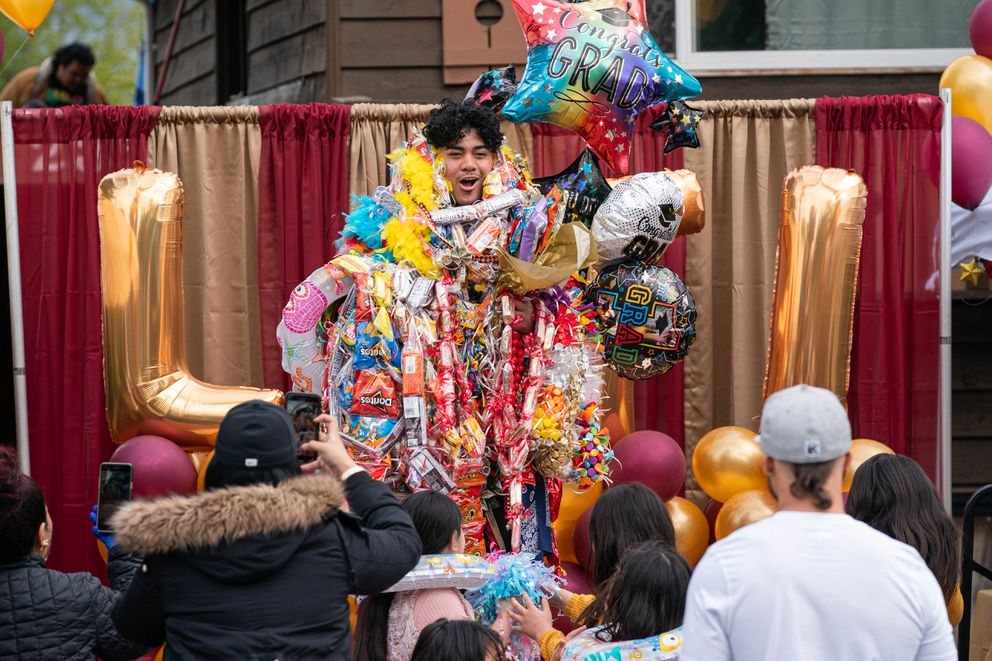 Dimond High senior Lafi Faualo is covered in leis to celebrate his graduation on Friday, May 22, 2020 in Anchorage. (Loren Holmes / ADN)