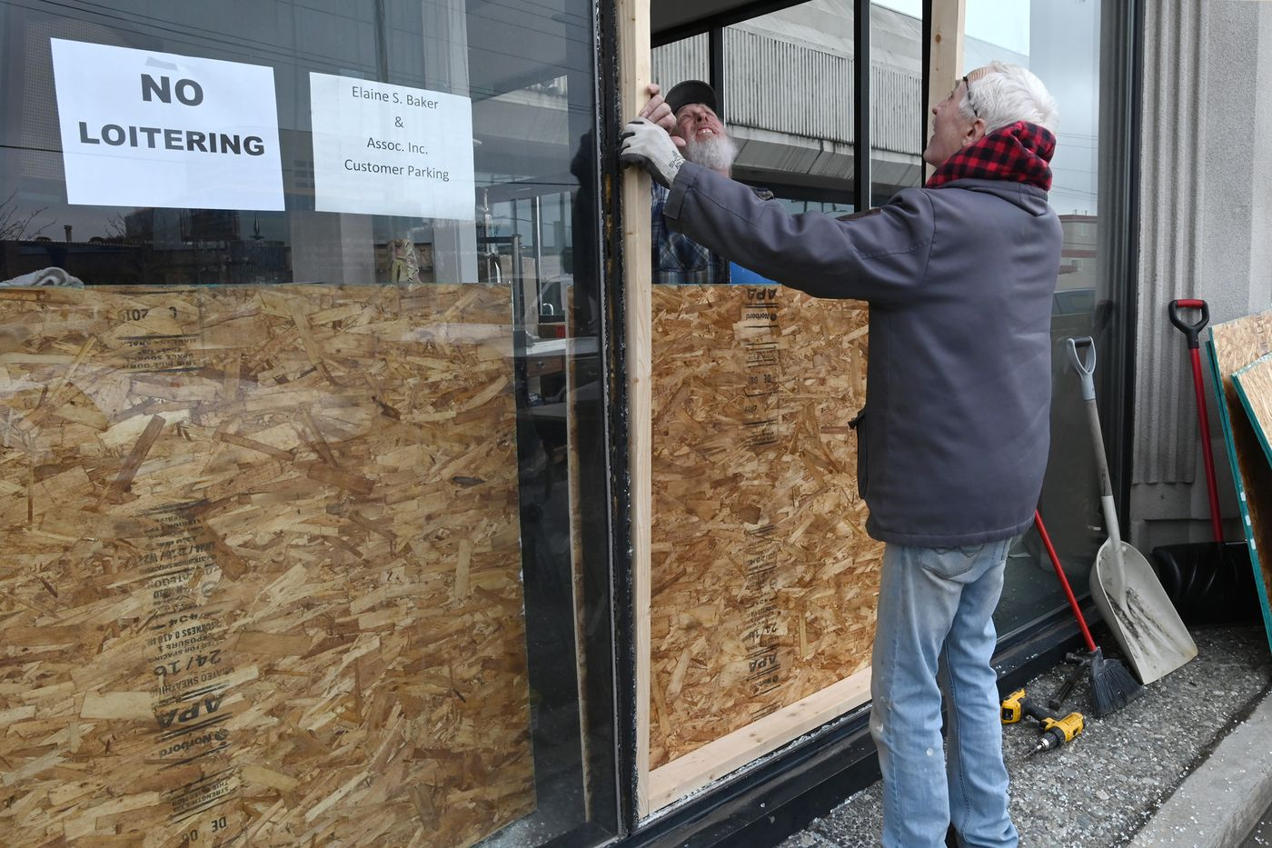 Paul and Vernon Wood of Wood Enterprises board up a smashed window at Elaine S. Baker and Associates, located on the corner of 5th & Gamble, after a vandal hurled a rock through it on Thursday, April 16, 2020. (Bill Roth / ADN)