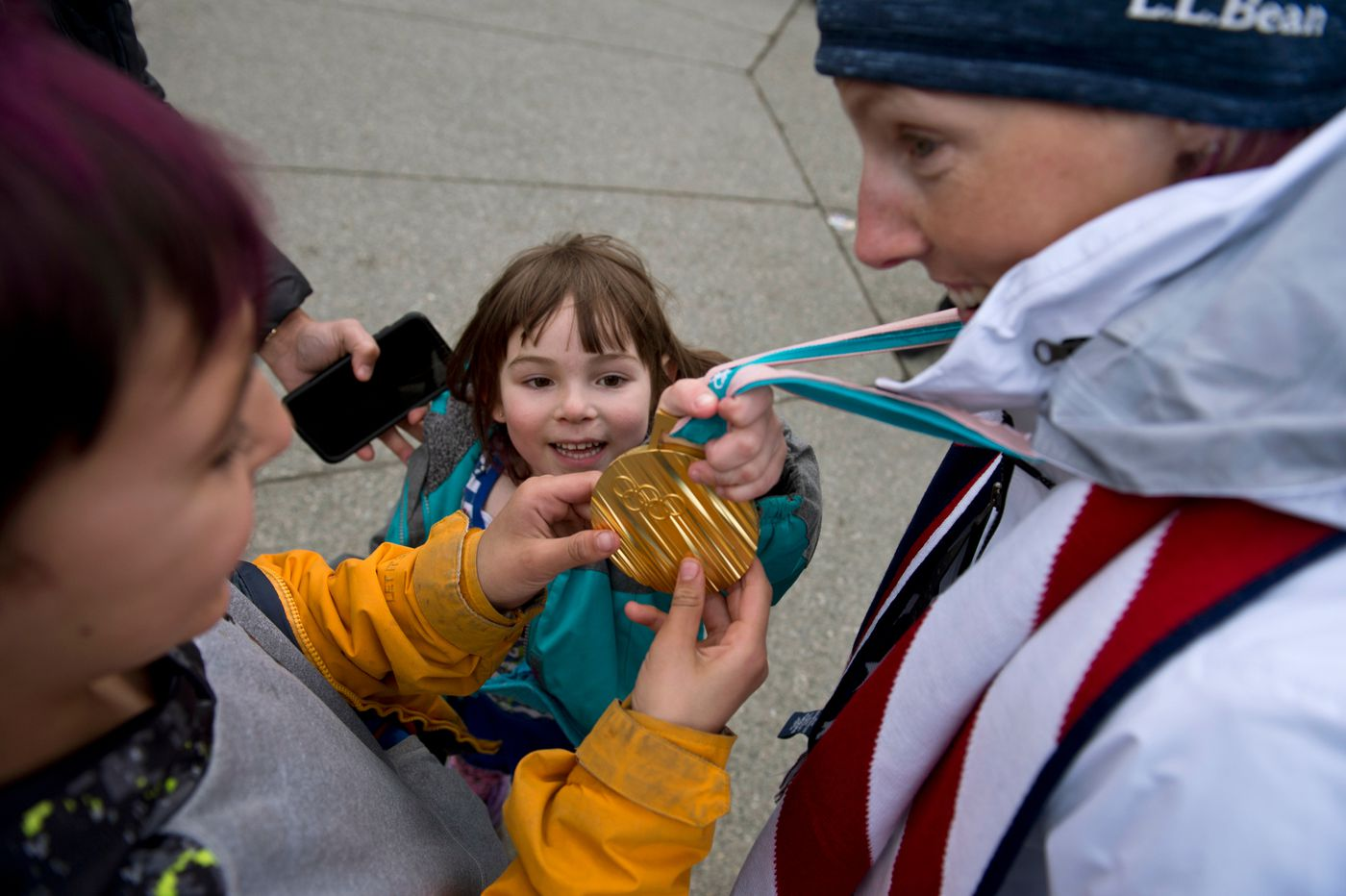 Adonna Bach, 4, center, and Zahn Bach, 7, examine Kikkan Randall's gold medal in Town Square on April 4. (Marc Lester / ADN)