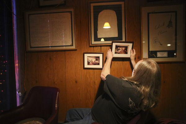 Scott Selman grabs a photograph from Club Paris' opening day in 1957 that was hanging on the wall behind him at his downtown Anchorage restaurant on Monday, Dec. 21, 2020. (Emily Mesner / ADN)