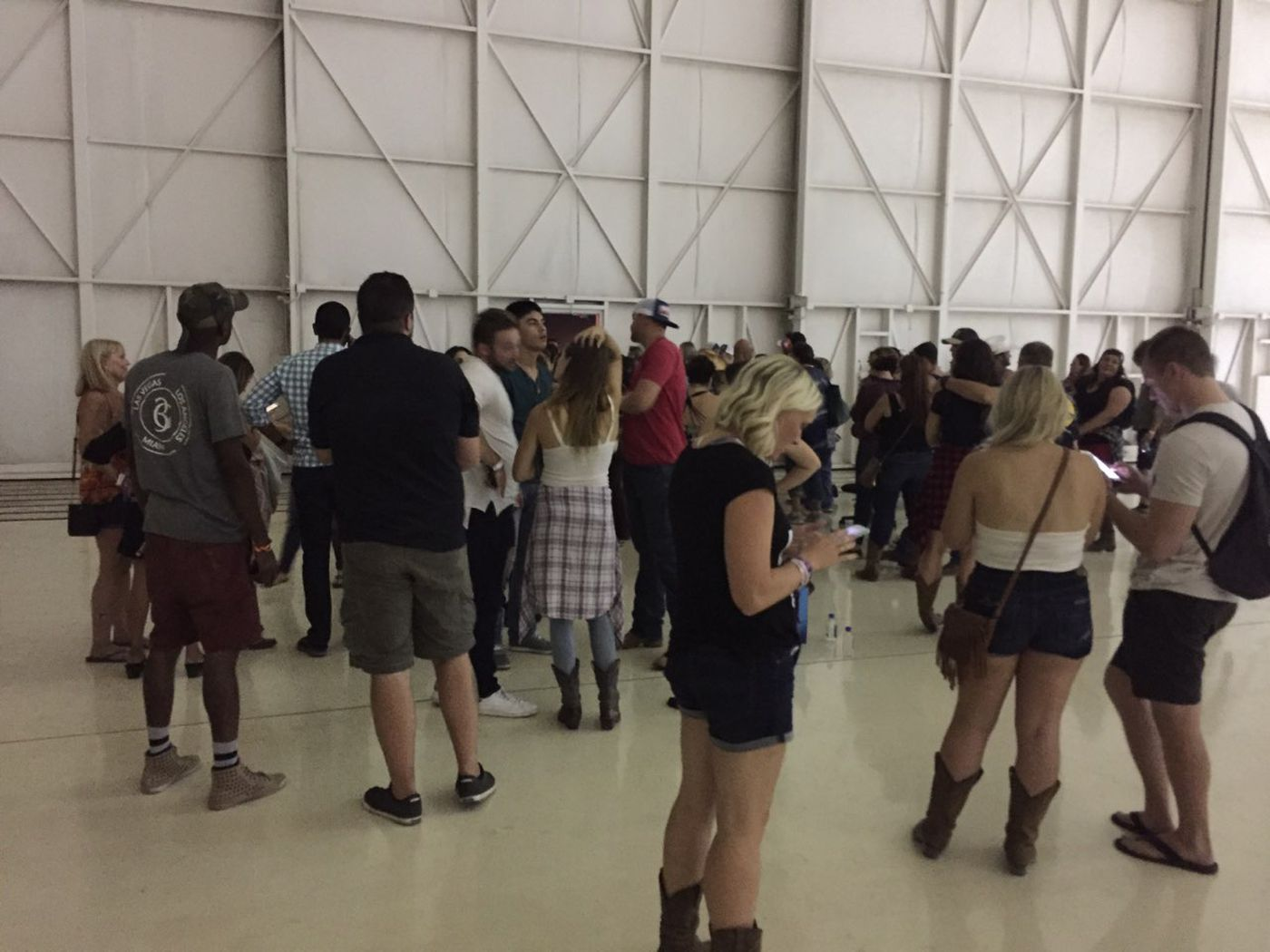 Some of the people who fled the gunfire at the Route 91 Harvest Festival in Las Vegas waited at an airplane hangar a few blocks away on Oct. 1. (Photo by Erik Ross)