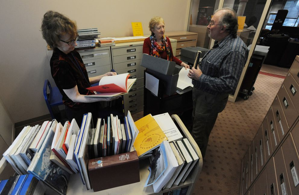 Jill Galbraith, Ingrid Gadpaille, and Doug McAllister sort through water-damaged books from the Alaska Collection at the Z.J. Loussac Public Library on Tuesday, Dec. 12, 2017. (Bill Roth / ADN)