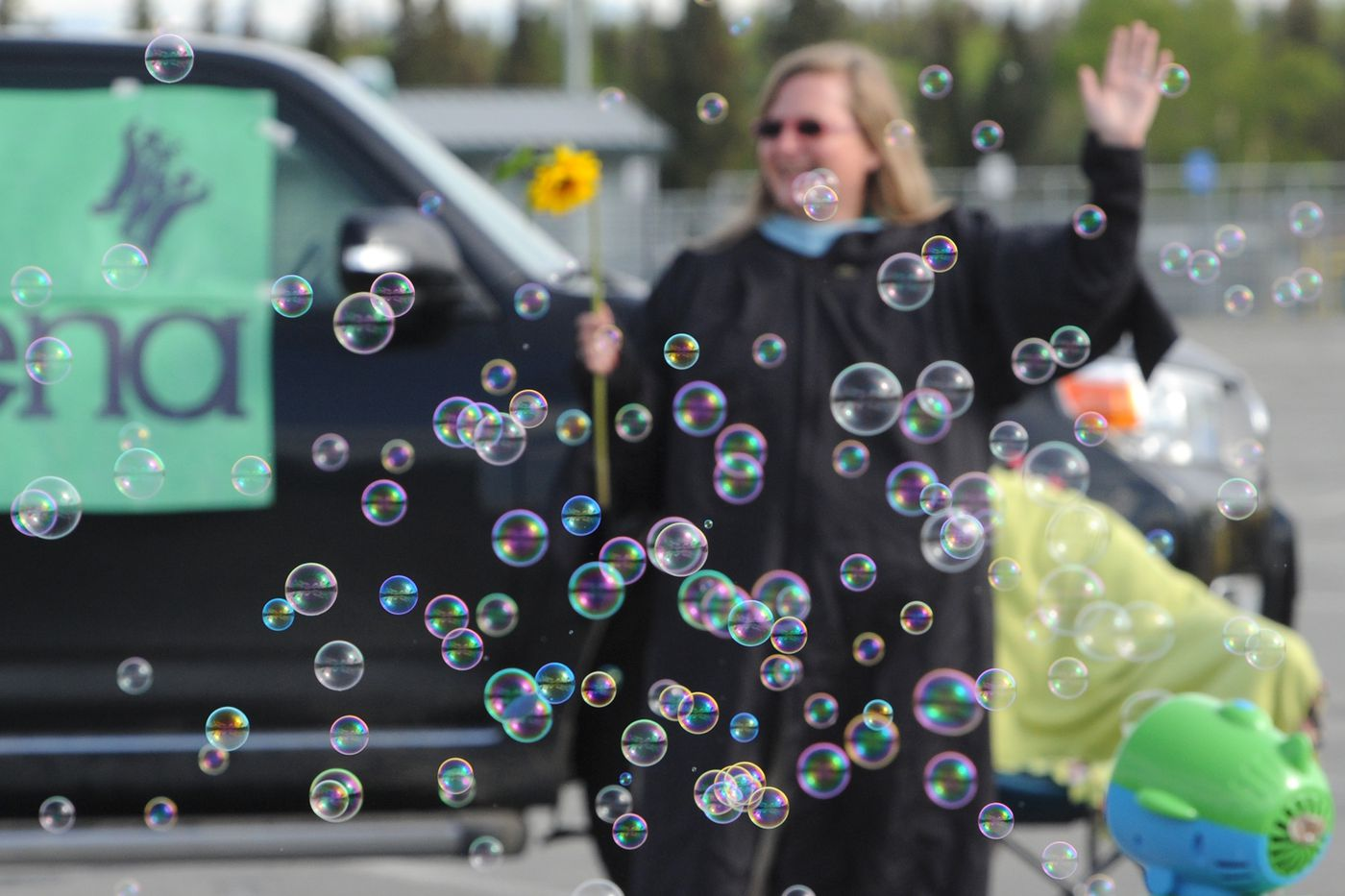 German Immersion teacher Evelyn Newhouse waved and shouted 'Congratulations ' as Service High School graduating seniors passed through the parking lot on Tuesday, May 19, 2020. (Bill Roth / ADN)