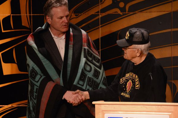Alaska Gov. Mike Dunleavy shakes hands with George Bennett Sr. after being given a Tlingit-style blanket on Wednesday, May 5, 2021. (James Brooks / ADN)
