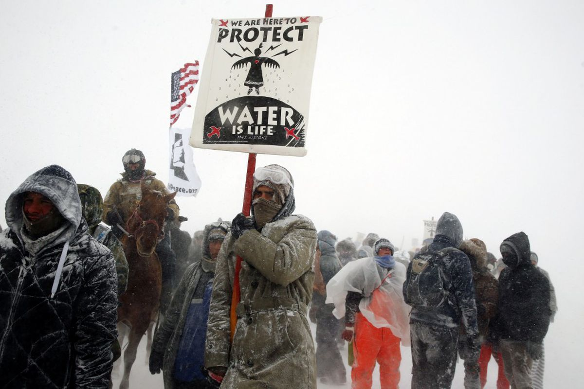 """Veterans join activists in a march just outside the Oceti Sakowin camp during a snowfall as """"water protectors"""" continue to demonstrate against plans to pass the Dakota Access pipeline adjacent to the Standing Rock Indian Reservation, near Cannon Ball, North Dakota, December 5, 2016. REUTERS/Lucas Jackson"""