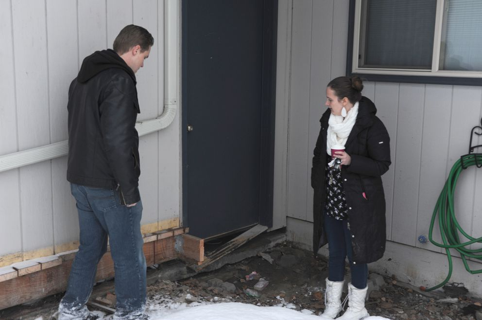 Albert Schoonbeek and Candice Roberson look at the corner of their house where the garage foundation dropped, ripping the structure away from the base. (Anne Raup / ADN)