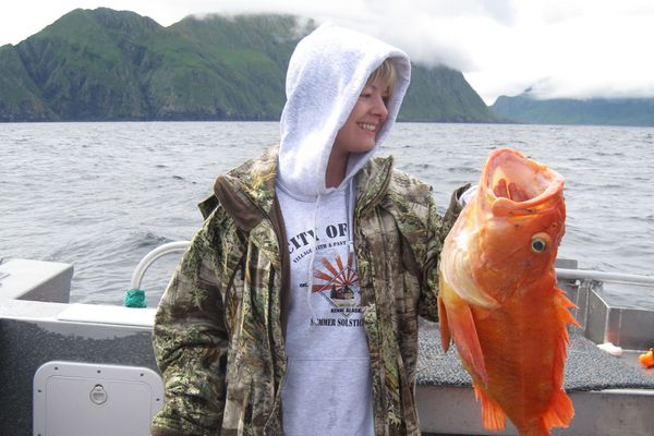 Christine Cunningham holds a yellow-eye and a lingcod during a fishing trip out of Homer. (Photo by Steve Meyer)