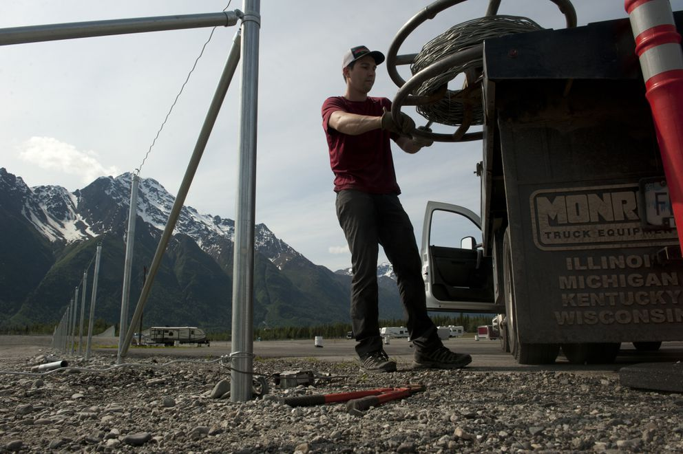 Aubrey Equevillex, from Mt. McKinley Fence, strings wire for the cyclone fence as the Alaska Raceway Park's new oval racetrack this week. (Bob Hallinen / Alaska Dispatch News)