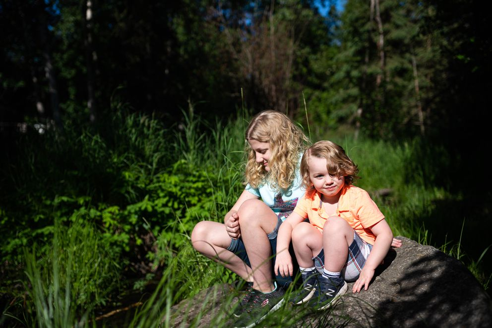 Karolina Knapp, 11, and her brother Johnnie Knapp, 4, sit on a rock next to a stream near their house on Saturday, June 27, in South Anchorage. Both children have health issues that make them especially vulnerable to complications from COVID-19. (Loren Holmes / ADN)