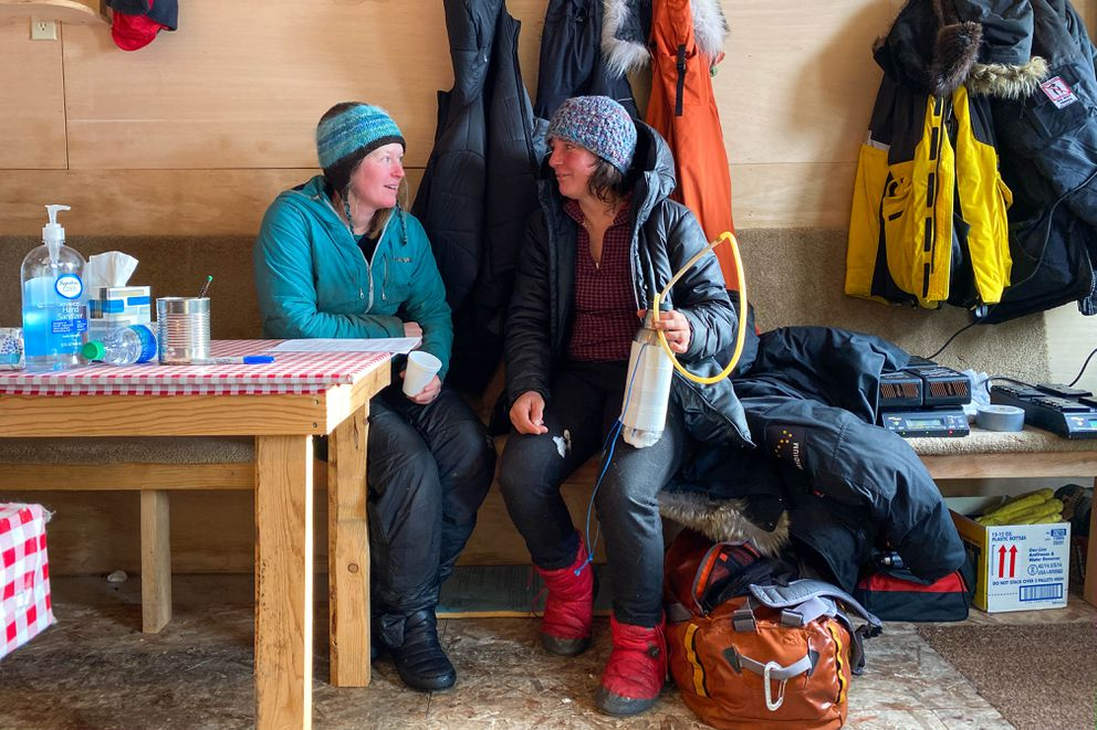 Paige Drobny talks with fellow musher Michelle Phillips at the Cripple checkpoint on Thursday, March 12, 2020 during the Iditarod Trail Sled Dog Race. (Loren Holmes / ADN)