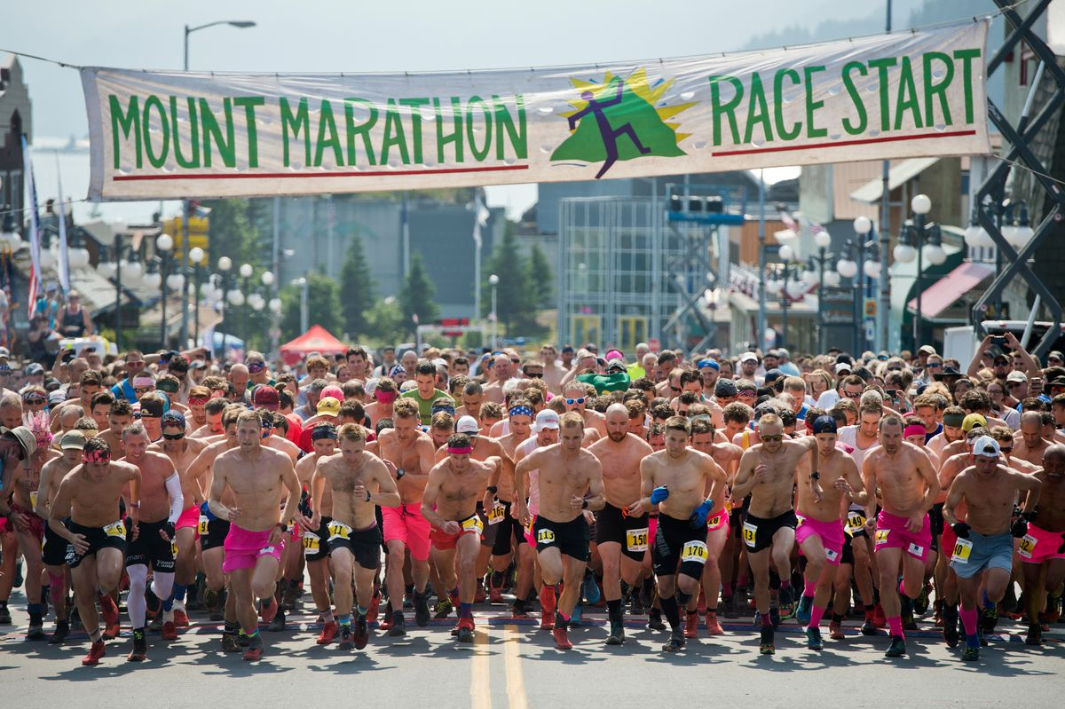 Runners in the first wave of the Mount Marathon men's race leave the starting line last year in Seward. (Marc Lester / ADN)