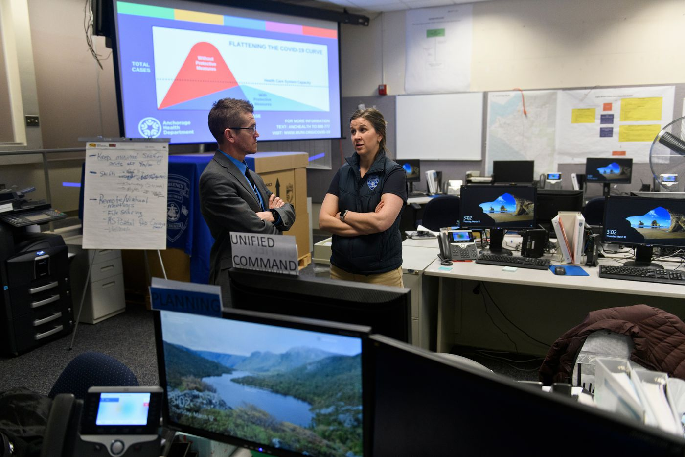 Systems analyst Mike Crawford, left, talks with Amanda Loach, director of Anchorage's Office of Emergency Management. City and school district officials held a press conference at the Anchorage Emergency Operations Center regarding measures in response to coronavirus on March 12, 2020. (Marc Lester / ADN)