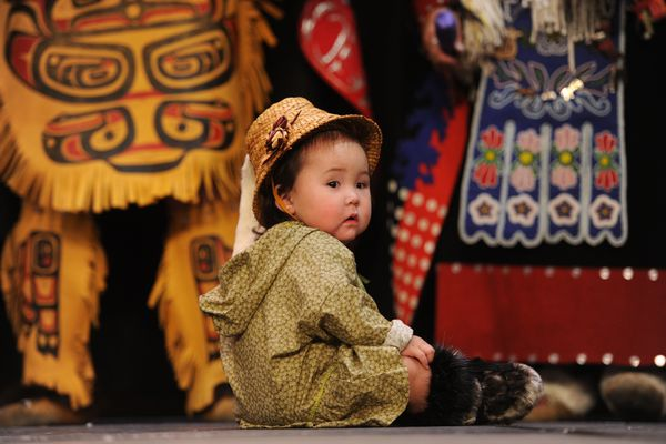 Almost one-year-old Ahbrylle Ahvakana-Walker sits on stage as the Lepquinm Gumilgit Gagoadim Tsimshian Dancers were the first group to perform during the Alaska Federation of Natives Quyana I on Thursday night, Oct. 23, 2014, at the Dena'ina Center in Anchorage. Quyana II will be on Friday night. (Bill Roth / Alaska Dispatch News)