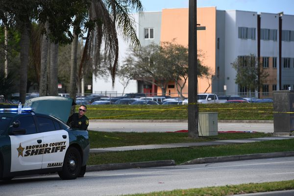 A Broward County Sheriff's officer is seen Thursday near Marjory Stoneman Douglas High School, top right, where 17 people were killed by a gunman Wednesday in Parkland, Fla. Washington Post photo by Matt McClain