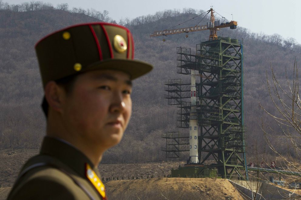 FILE - In this April 8, 2012, file photo, a soldier stands in front of the Unha-3 rocket at a launching site in Tongchang-ri, North Korea. (AP Photo/David Guttenfelder, File)