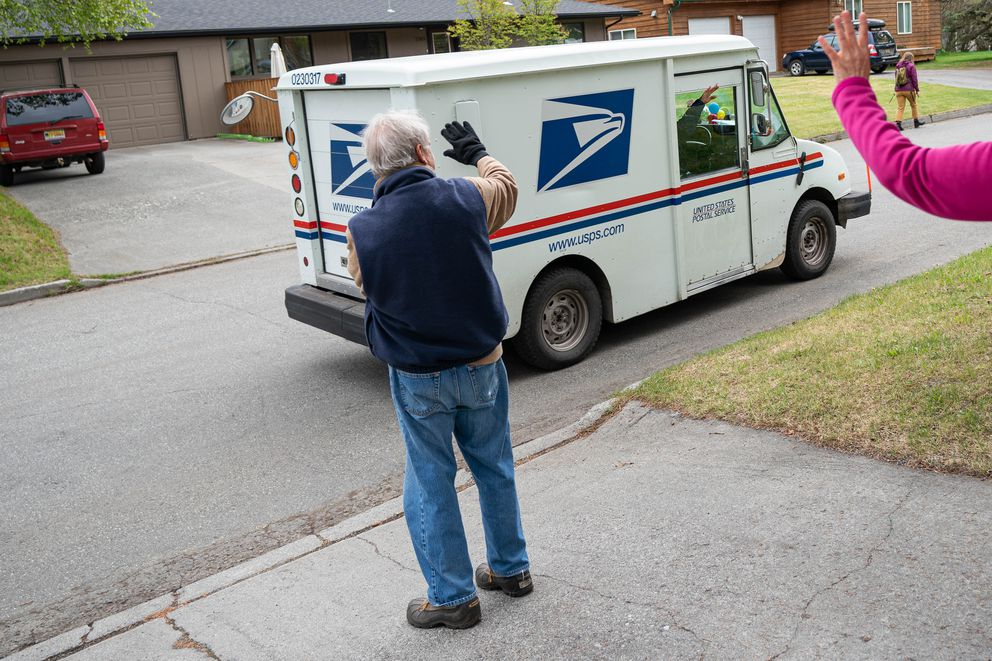 John Sroufe and Diane DiSanto wave to mail carrier Weeze Smoke on Saturday, May 23, 2020 in Turnagain. Smoke has delivered the mail in this neighborhood for the past 15 years and Saturday was her last day on the job before retiring. (Loren Holmes / ADN)