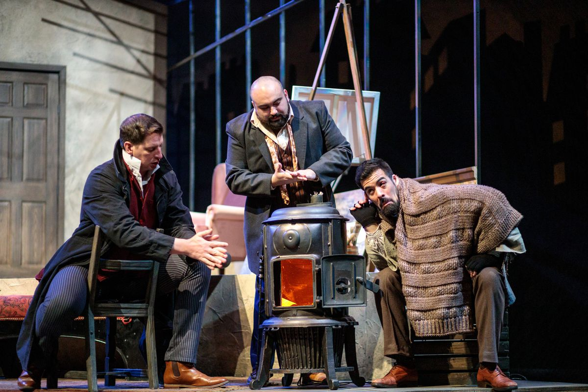 Coline (Andrew Potter), Rodolfo (Peter Scott Drackley) and Marcello (Luis Alejandro Orozco) warming by the fire on a cold night in Paris in Anchorage Opera's