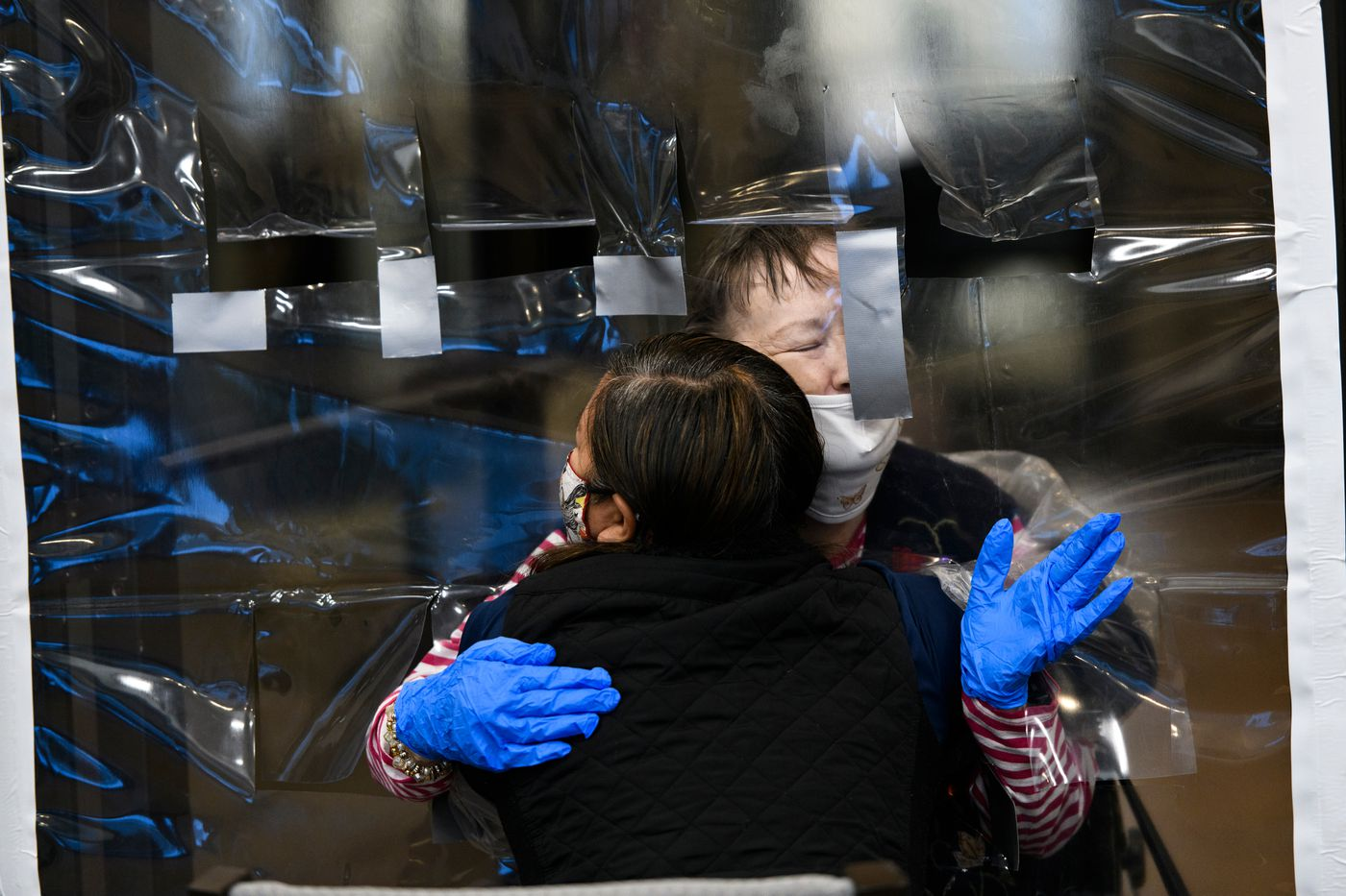 DECEMBER 2. Cordelia Scott, facing, hugs her daughter-in-law, Pheng Scott, through a sheet of plastic at Aspen Creek, an assisted living center. This was the second session of the 'hugging wall ' at Aspen Creek, designed to keep its senior population safe from COVID-19 but in contact with family members. (Marc Lester / ADN)