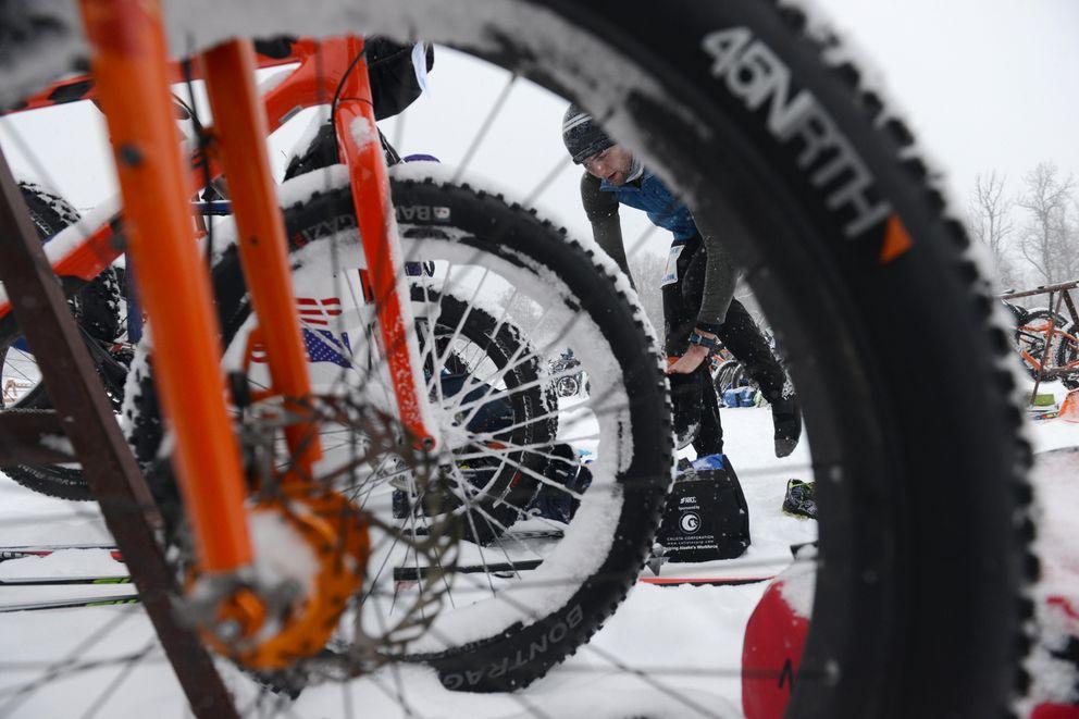 Jahn Corbyn changes footgear as he transitions from running to his fat bike in the Tri-Flake Triathlon at Kincaid Park in Anchorage, Alaska on Saturday, January 21, 2017. (Bob Hallinen / Alaska Dispatch News)
