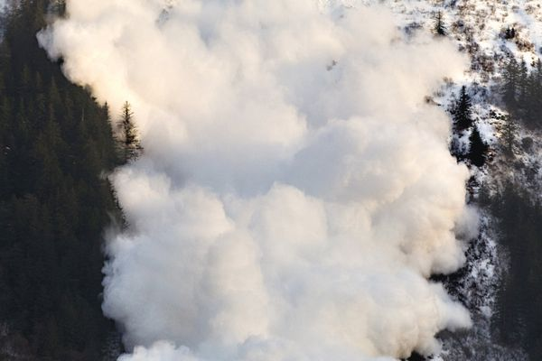 In this photo taken Monday, Jan. 2, 2012, an avalanche descends down Snow Gulch Creek along Thane Road during avalanche control by the Department of Transportation in Juneau, Alaska. Several large dust clouds reached road level during the firing of about 24 105mm howitzer shells. (AP Photo/The Juneau Empire, Michael Penn)