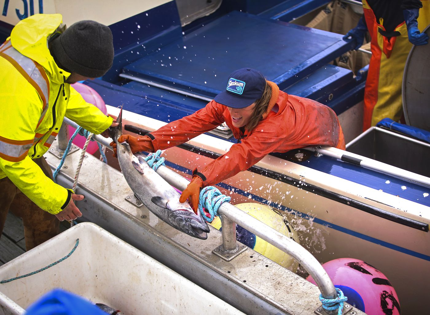 Nelly Hand gives a Copper River king salmon to Ezekiel Brown, captain of the F/V Lucid Dream, while offloading salmon to his tender before heading back to Cordova on Thursday, May 20, 2021. (Emily Mesner / ADN)