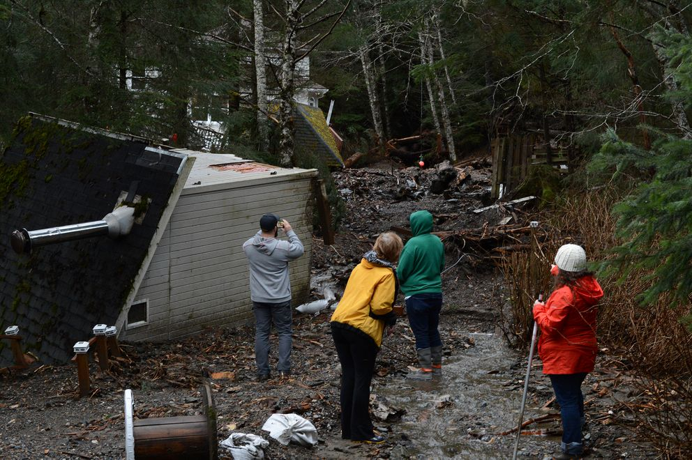 Members of Juneau's Mountainside Drive neighborhood inspect the damage after an overnight mudslide on Wednesday morning. A record amount of rain fell on Southeast Alaska on Tuesday, triggering avalanches, mudslides and small floods. (James Brooks / ADN)