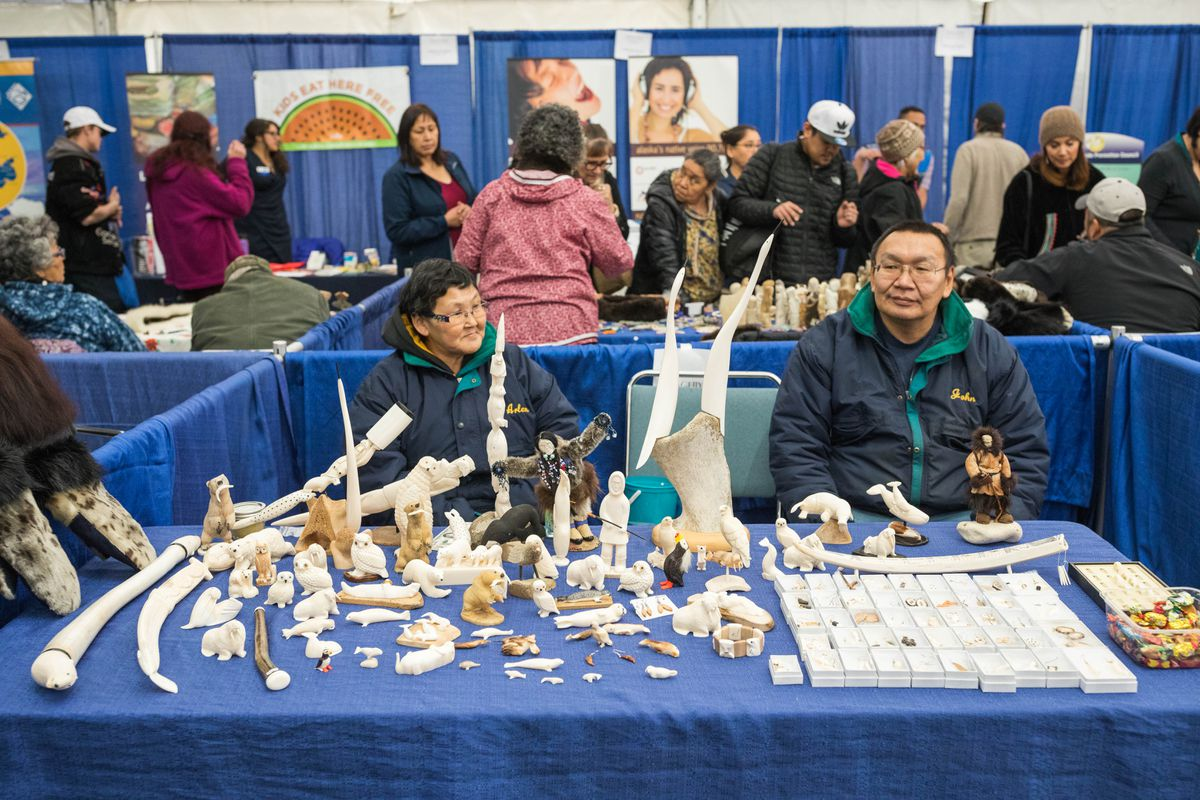 Arlene and John Waghiyi offer St. Lawrence Island walrus ivory carvings for sale in the arts and crafts tent at the Alaska Federation of Natives convention in Fairbanks recently. (Loren Holmes / Alaska Dispatch News)