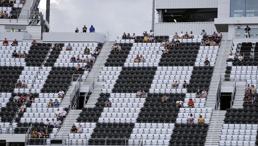 Fans socially distance during a NASCAR Cup Series auto race at Daytona International Speedway, Sunday, Aug. 16, 2020, in Daytona Beach, Fla. There were a limited amount of fans allowed. (AP Photo/Terry Renna)