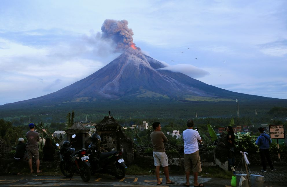 Residents watch the Mount Mayon volcano as it erupted anew Thursday. REUTERS/Romeo Ranoco